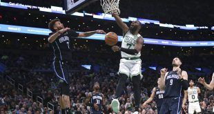 Magic players watch Celtics player dunk ball