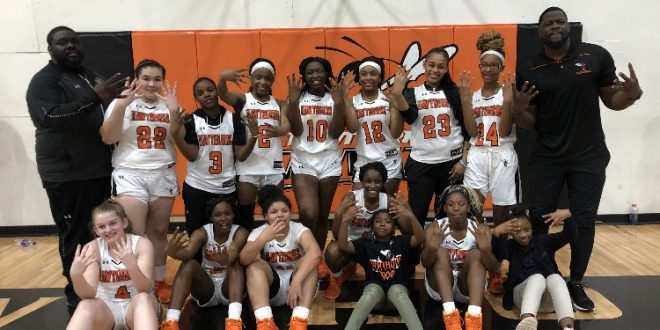 Girls basketball team poses after win