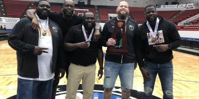 Hawthorne coaches pose with trophy