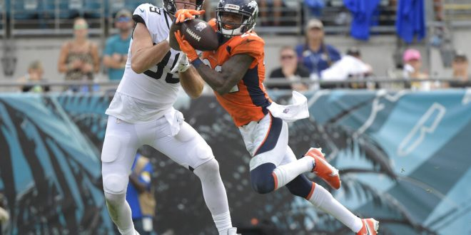 Jaguars fight Broncos for possession of the ball